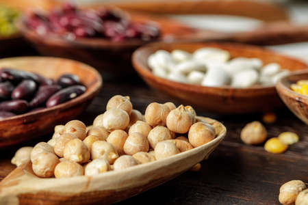 Wooden spoons with grains and beans on wooden table close up