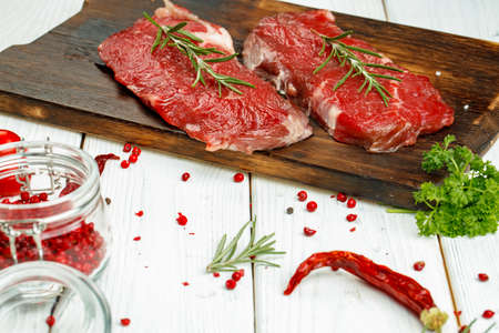Barbecue veal steaks with rosemary on wooden board. Raw meat