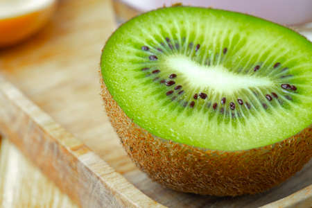 Half of fresh kiwi on wooden board close up