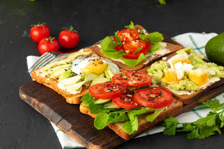 Fried toasts with avocado and egg, and with cream cheese and tomatoes on wooden board Foto de archivo