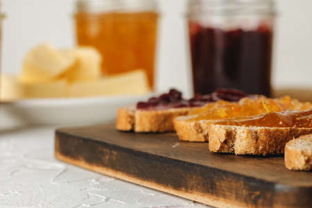 Slice of bread covered with fruit jam on wooden board close up