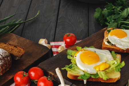 Fried egg in frying pan with sliced bread on black wooden table