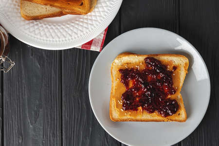 Toasted bread slices with berry jam on dark wooden table Foto de archivo