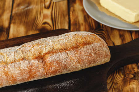 Fresh baked loaf of bread with butter bar on wooden table