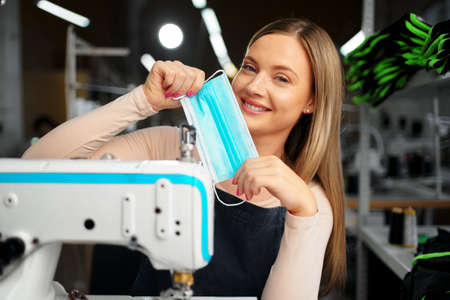 Smiling young blonde seamstress putting on medical protective mask Zdjęcie Seryjne