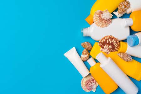 Sunscreen cream bottles with sea shells on blue background Zdjęcie Seryjne