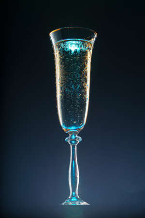 Glass full of champagne on black background