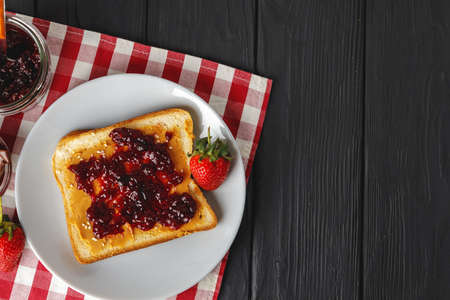 Toasted bread slices with berry jam on dark wooden table 스톡 콘텐츠