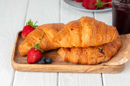 Fresh croissant decorated with berries on white wooden board