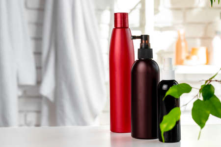 Cosmetic bottles against white bathroom wall background front view 免版税图像