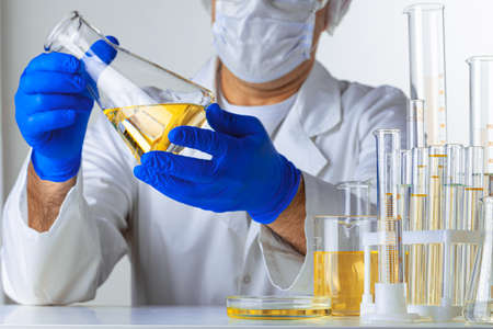 Scientist hands holding some liquid in a glassware in laboratory for analysis, close up Banco de Imagens
