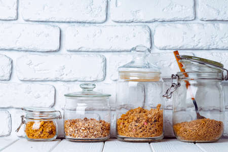 Glass jars with granola and muesli, front view
