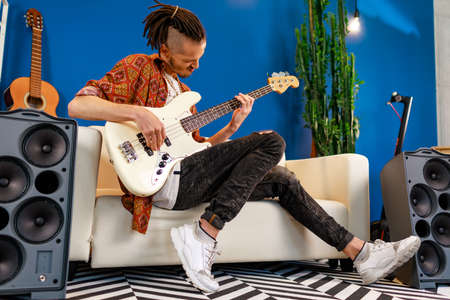 Young caucasian man with dreadlocks playing electric guitar in his room