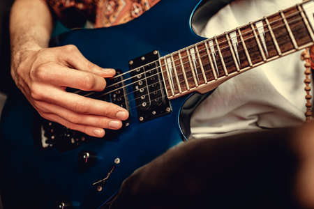 Close up photo of male hand playing electric guitar in the dark 스톡 콘텐츠