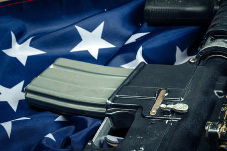 U.S. battle flag and assault rifle on the wooden table. Close up.