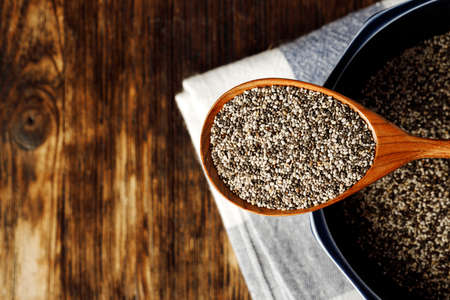 Chia seeds in a bowl with wooden spoon