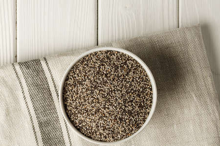 Bowl with raw chia seeds close up