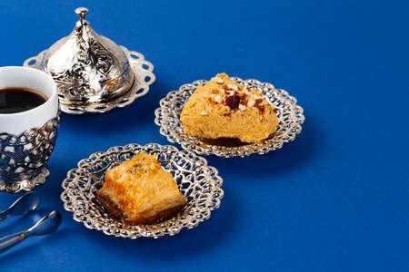 Halva dessert with tea cup on blue background close up