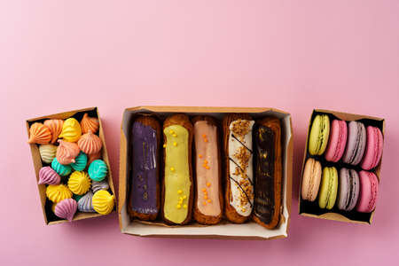 Carton boxes with eclair cakes and cookies on pink surface close up