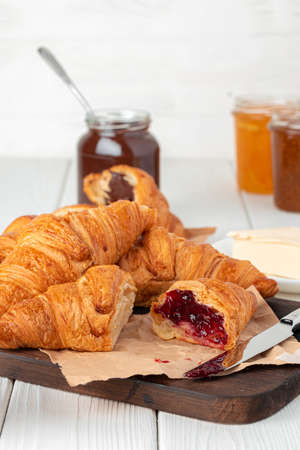 Fresh croissants with berry jam on dark wooden board, close up