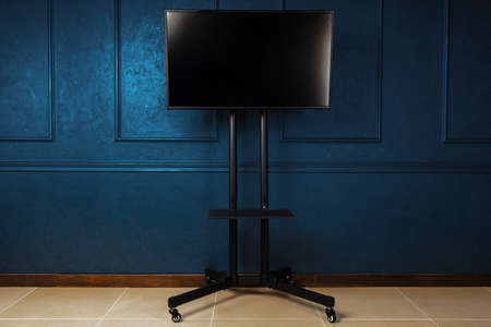 Tv set on metal stand against dark blue wall Stock fotó