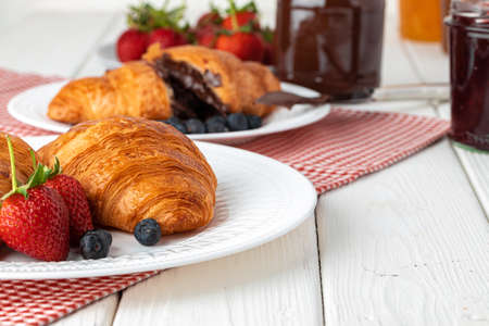 Fresh croissant decorated with berries on white wooden board close up