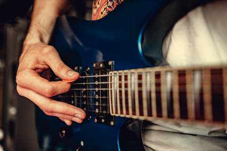 Close up of male hand playing electric guitar in the dark Stock fotó
