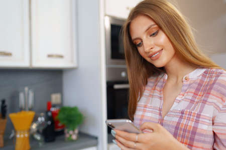 Pretty young woman in casual clothes using her smartphone in kitchen