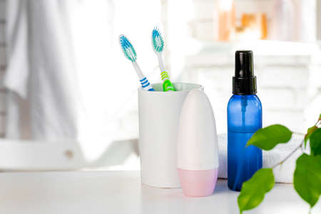 White cup with toothbrushes and towels in bathroom