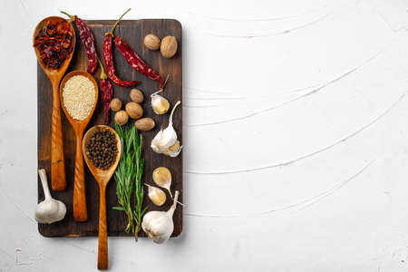 Red chili peppers and other spices on white textured background, top view