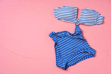 Blue striped monokini on pink pastel background with copy space