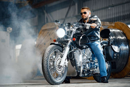 Bearded motorcyclist in black leather clothing with his motorbike