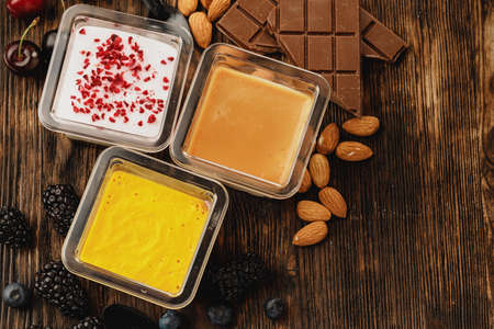 Assortment of delicious dessert boxes on wooden table