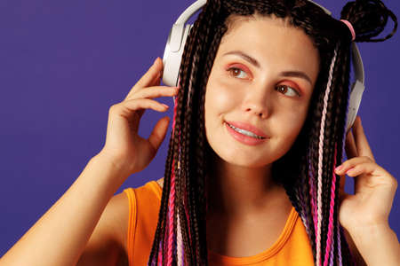 Young caucasian woman with african cornrows listening to music with headphones