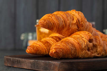 Fresh croissants on wooden board close up