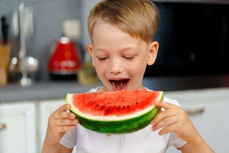 Little boy eating watermelon piece in the kitchen