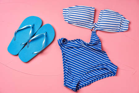 Blue striped monokini with blue flip-flops on pink background