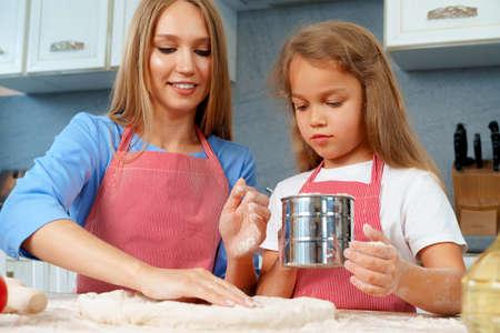 Mother and her little daughter preparing dough in kitchen Reklamní fotografie