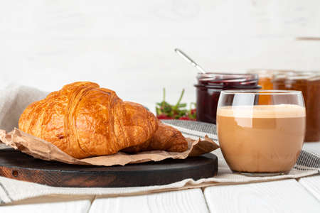 Tasty croissant with cup of coffee with milk on kitchen table 스톡 콘텐츠