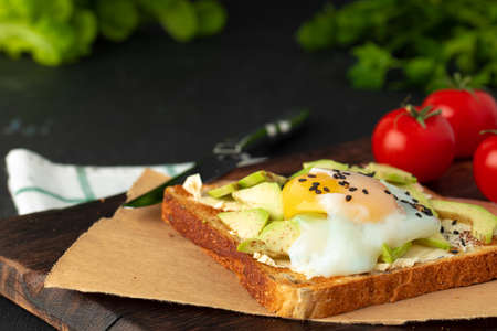Sandwich with fried egg and avocado pieces