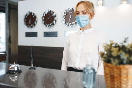Woman hotel receptionist wearing medical mask to protect from coronavirus infection