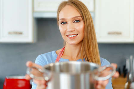 Attractive young blonde woman checking cooked food Reklamní fotografie