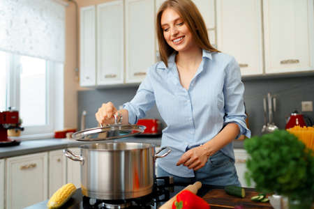 Nice young woman cooking something by the stove in her kitchen