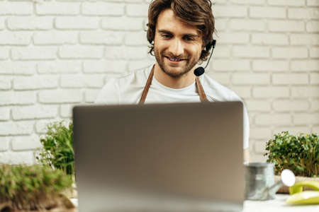 Handsome bearded man sells plant sprouts and seedlings online using laptop Archivio Fotografico