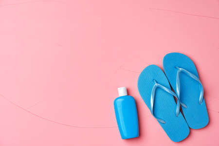 Blue cosmetic bottle with sunscreen cream and flip-flops on pink background 版權商用圖片