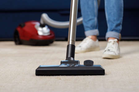 Close up of a woman vacuum-cleaning the carpet 版權商用圖片