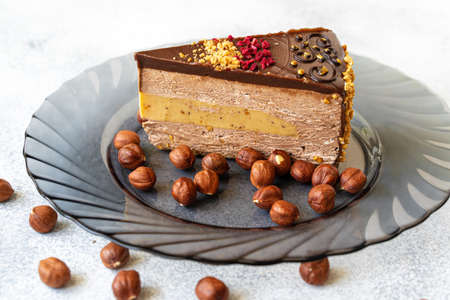 Piece of chocolate cheesecake with nuts close up