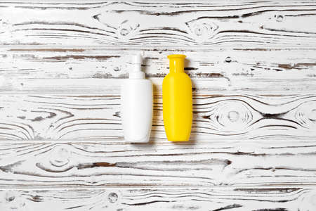 Sunblock cream cosmetic bottles on wooden surface
