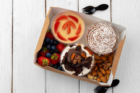 Assortment of desserts in boxes on white wooden background 版權商用圖片