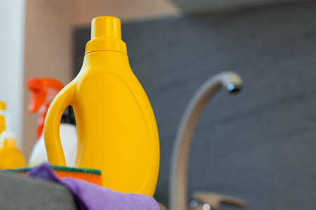Household chemicals product bottles standing near the kitchen sink 版權商用圖片